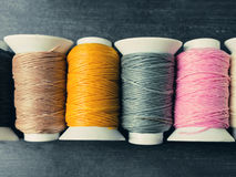 black-brown-yellow-grey-pink-white-thread-rolls-woo-top-view-colored-sewing-threads-wooden-background-81461202